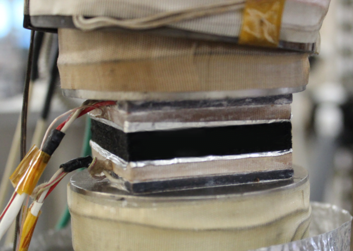 A sample is sandwiched between two heat flux transducers.